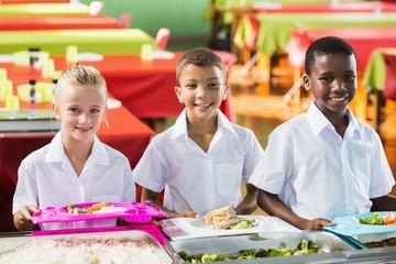 Portrait of school kids having lunch during break time