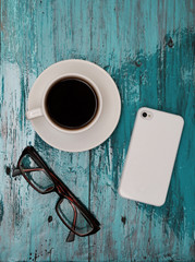Cup of cofee and phone on tiffany wood background