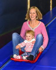Mama mit Kleinkind auf der Rollschlittenbahn im Indoor-Freizeitpark