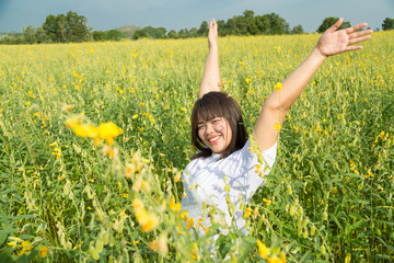 asian young  chubby women is raising arms to the sky in yellow f