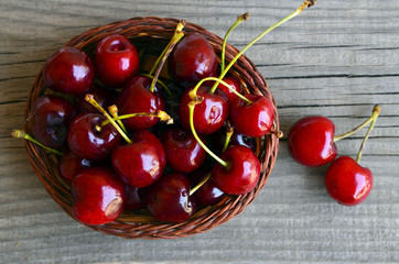 Fresh organic cherries berries in a basket on old wooden background.Selective focus.