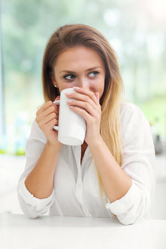Young woman with coffee in kitchen