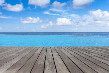 piscine à débordement margelle bois avec vue sur l'océan