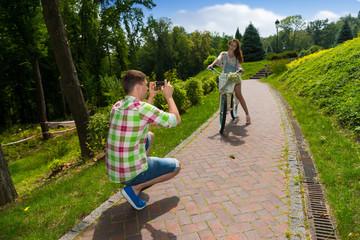 Man taking a photo of his girfriend sitting on a bike