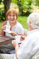 Senior couple enjoying cup of coffee outdoors