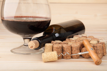 Corkscrew, corks, bottle of wine and a glass. Selective focus