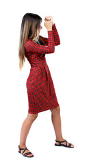 skinny woman funny fights waving his arms and legs. Isolated over white background. The girl in red plaid covers his face with his hands in a fighting stance.