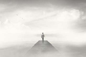 Man walking on a boardwalk in the fog