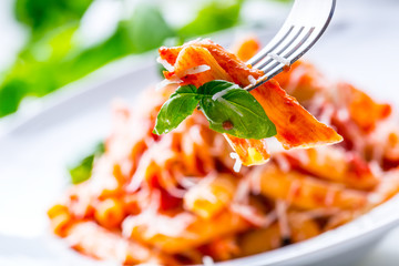 Pasta Penne with Tomato Bolognese Sauce, Parmesan Cheese and Basil on a Fork. Mediterranean food.Italian cuisine.