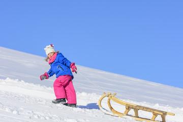 kleines Mädchen zieht ihren Schlitten den Hang hinauf