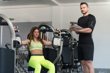 Woman Train Shoulders On Machine With Personal Trainer