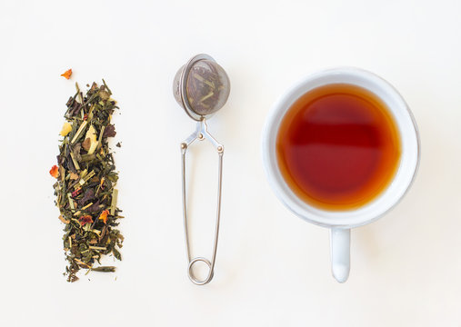 Cup of tea, loose leaf and tea strainer on white background