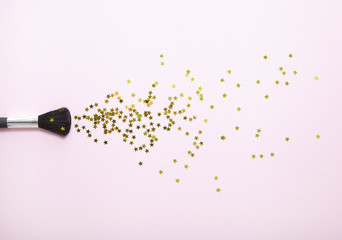 Aerial view of a powder make up brush with gold sequin stars spilling out over a pastel pink background