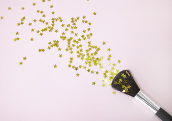 A powder make up brush with gold glitter stars spilling out over a pastel pink background