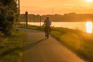Radfahrer bei Sonnenuntergang am Flussufer