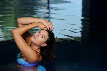 Attraktive junge Frau posiert in einem Swimmingpool