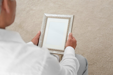 Man holding photo frame. Memories and nostalgia concept