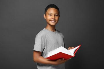 Cute boy reading book on grey background