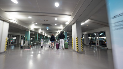 People with luggage walking on the moving walkway at the airport terminal of Seoul, South Korea