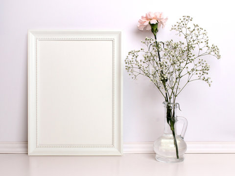 White frame mockup with flowers. Front viw of the empty white frame