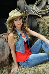 Sexy cowgirl relaxing on haystacks inside stable.