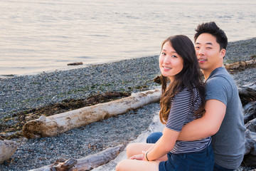 Young Asian Couple Sitting on Driftwood on Beach. Copy space.