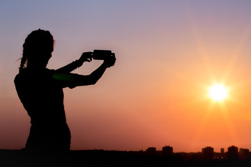 Silhouette of female taking photos of sunset with smart phone. Summer, travel and technology concepts.
