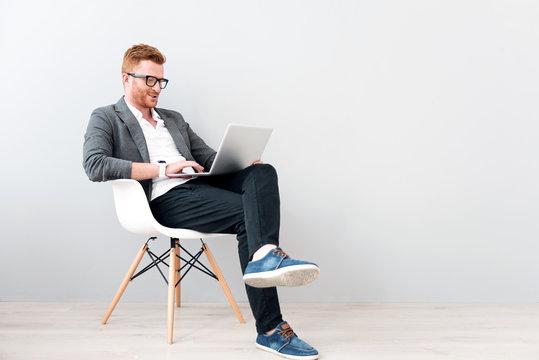 Pleasant positive business man using laptop