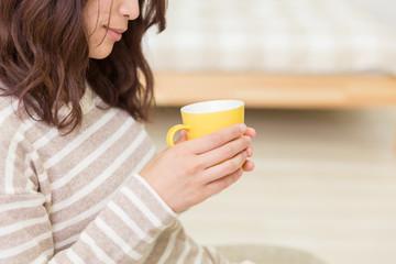 部屋でお茶を飲む女性 手元