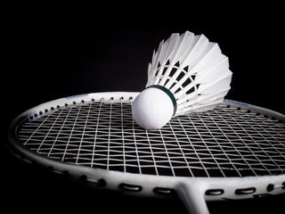 racket with string and shuttlecock on black background