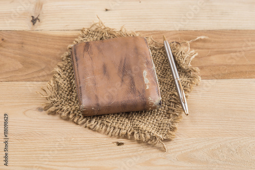 old wallet with steel pen on wooden background, leather wallet