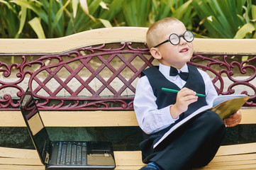 funny cute boy with glasses sitting with a laptop pre-school education