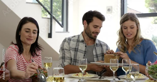 """Friends interacting while having a meal at dining table ..."