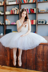 Dancer in a tutu and dress in library using phone