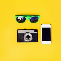 Fashion accessory. Sunglasses, vintage camera and smartphone on