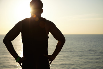 Silhouette of young dark-skinned athlete relaxing after running workout at seaside, standing on coastline and enjoying beautiful sunset over sea, holding hands on his waist. Image with sunlight effect