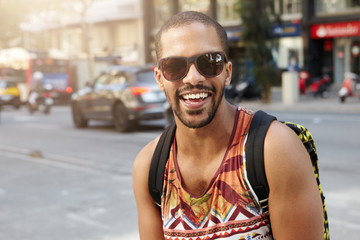 Outdoor portrait of fashionable dark-skinned traveller dressed like hipster, wearing backpack and stylish shades, walking down a busy street, looking happy and cheerful, having fun in a big city