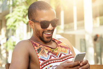 Young attractive dark-skinned male looking happy holding his cellphone, receiving good news from sister about birth of his niece. African man in trendy sunglasses liking funny posts on social network