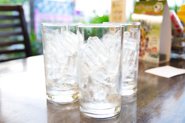 Ice in the glasses placed on wooden table,focus front glass.