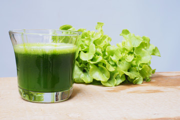 Close up of a glass of mixed green vegetable juice on a wooden table.