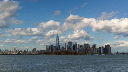 Fotomurales - Time lapse of New York City's Lower Manhattan Financial District skyscrapers and clouds with Ellis Island from New York harbor