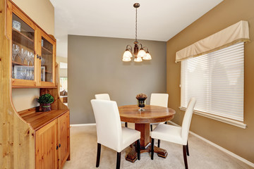 Cozy dining room with white chairs and vintage round table.