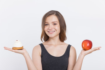 Girl holding apple and cupcake