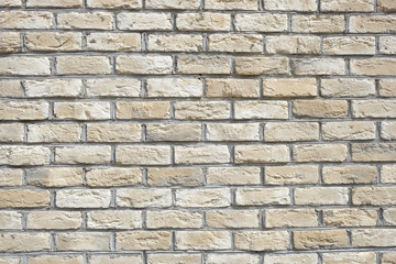 Wall from beige bricks front view closeup horizontal photo