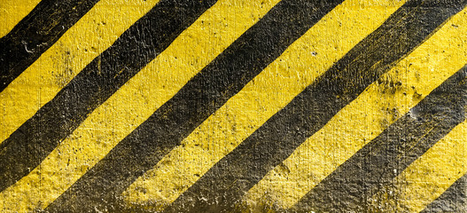 striped black and yellow background. Industrial striped road warning yellow-black pattern. Caution sign on the street, warning and dangerous.