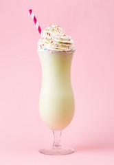 Glass of vanilla milkshake with whipped cream on pink background