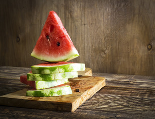 Triangular pieces of a water melon on a kitchen board and a wooden background