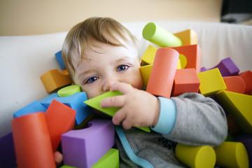 Happy baby boy burried with foam toys
