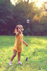 Little girl playing with soap balloons in nature.