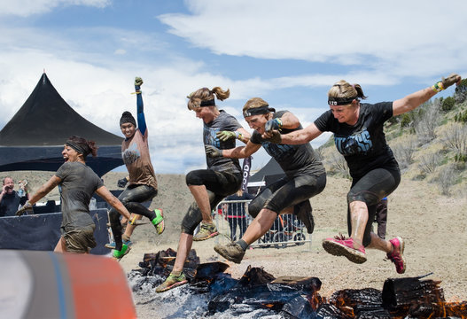 Spartan Race, Fort Carson, CO May 2015 Five women competitors jumping over fire to the finish line with enthusiastic supporter.